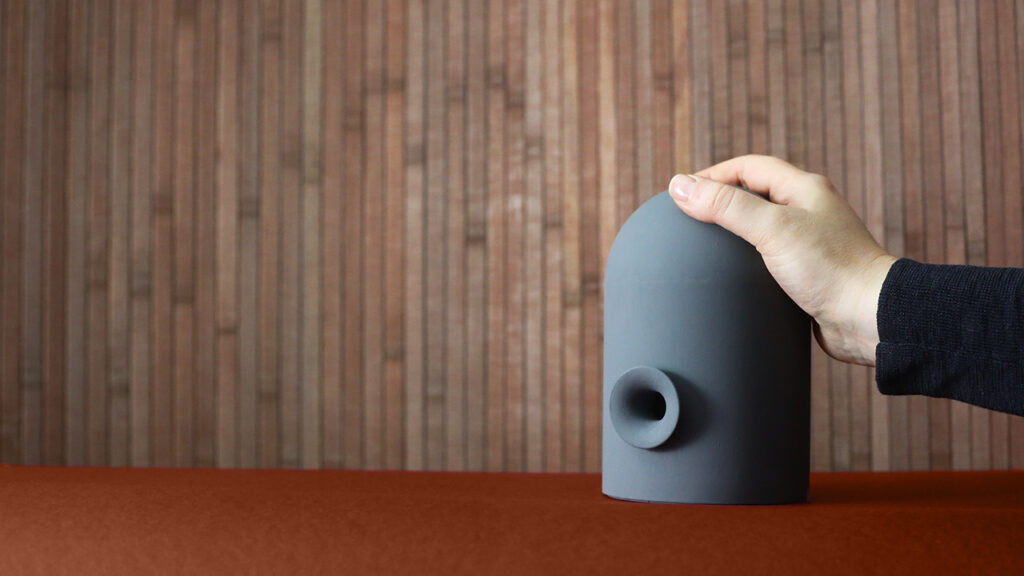 hand on speaker-like object, a so-called attachment device