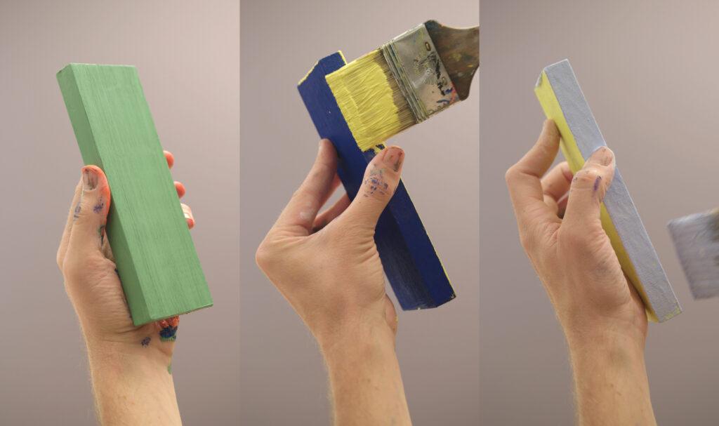 Drie handen die stukken hout vasthouden en in verschillende kleuren verven.